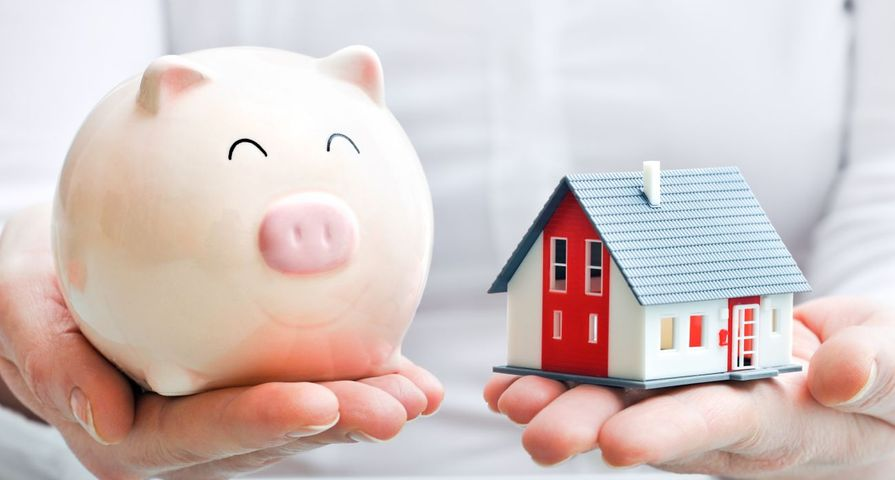 Person Holding a Piggy Bank and Tiny Home