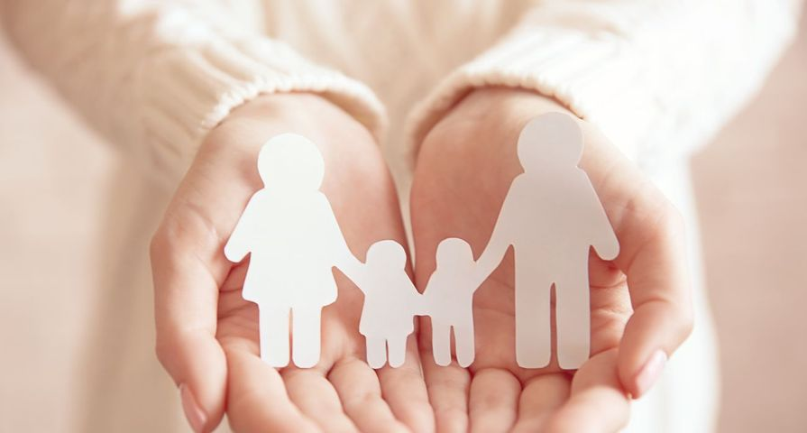 Woman Holding Paper Family in Hands