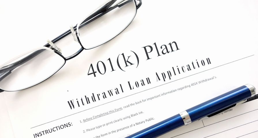 401K Loan Application with Pen and Glasses
