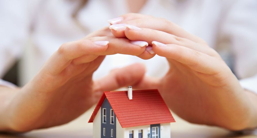 Womans Hands Covering Mini House