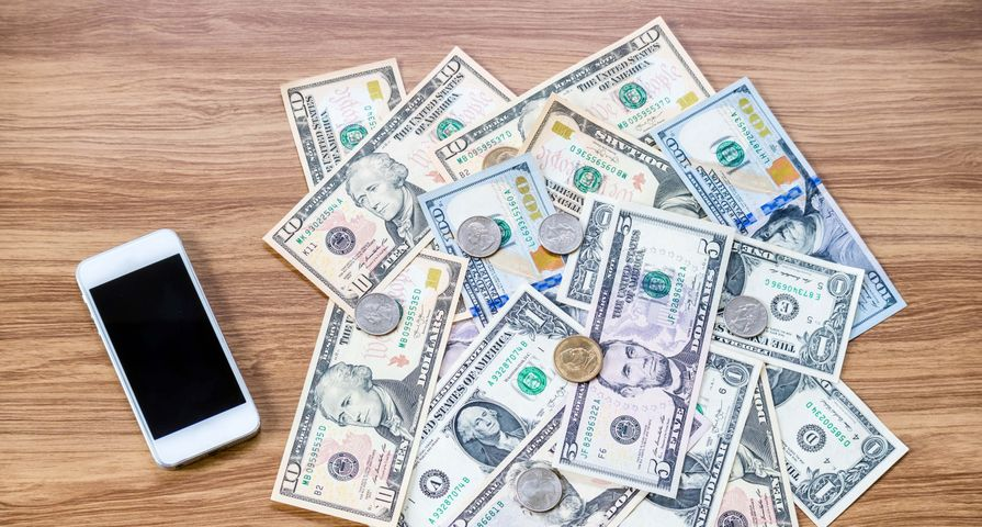 Cash Money on Table by Mobile Phone
