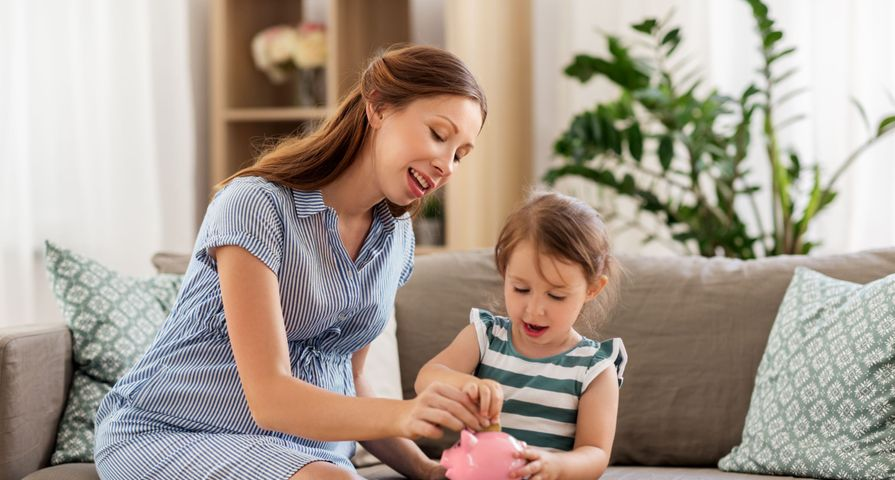 Single Mom and Child Putting Money in Piggy Bank