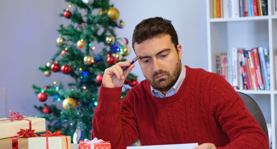 Man Upset Looking at Bills with Christmas Tree