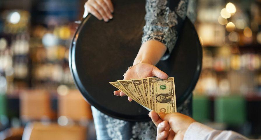 Customer Tipping Waiter in Restaurant