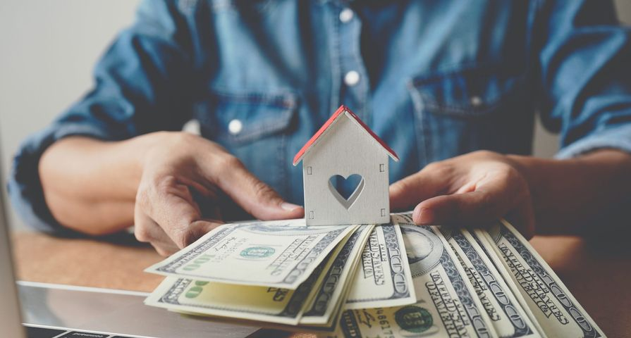 Man Holding Mini Home & Money