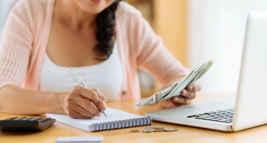 Woman Recording Cash Spent on Notepad