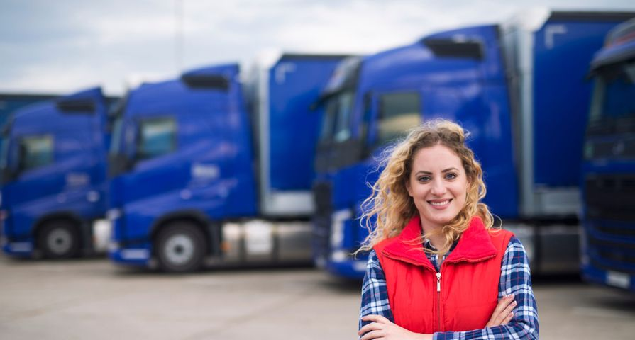 Female Trucker Smiling in Front of Trucks
