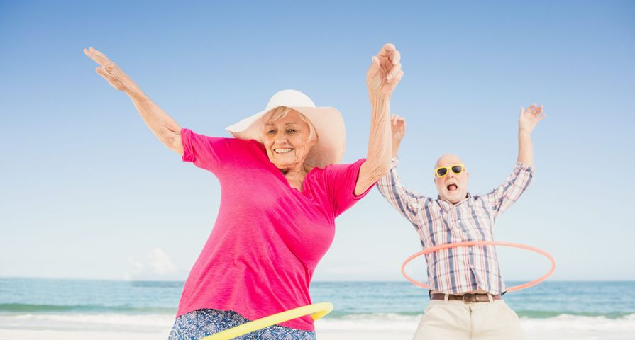 Retired Couple Hula Hooping on Beach